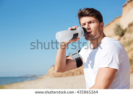 Serious young sportsman sitting and drinking water on the beach