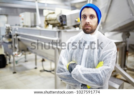 Serious young staff of seafood production factory looking at camera by workplace