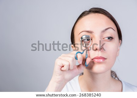 Serious Young Woman Crimping her Right Eyelashes Using Lash Curler While Looking to the Right of the Frame on a Gray Background. - stock photo