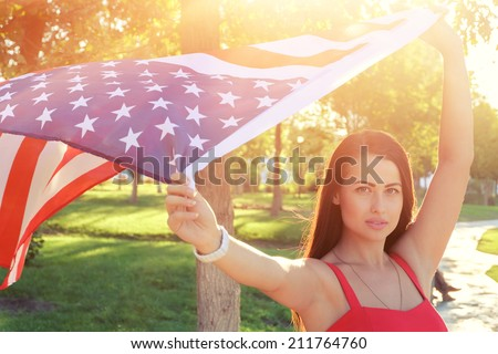 Serious young woman holding american flag flying by the wind - stock photo