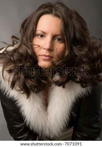 serious young woman in fur coat on gray background