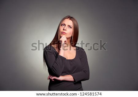 serious young woman pondering over something. studio shot against dark grey background - stock photo