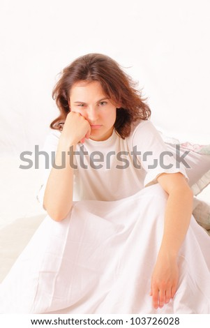 Serious young woman sitting in bed - stock photo