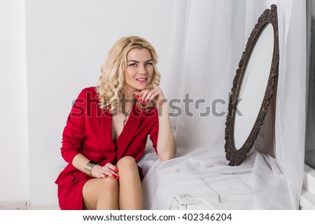 Serious young woman sitting in the studio look a serious sadness. a psychological portrait, looking in the mirror white background red jacket - stock photo