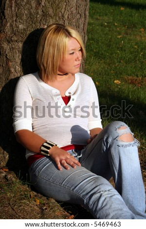 Serious young woman sitting on the ground near a tree, with her face turned to her left toward the sunlight. - stock photo