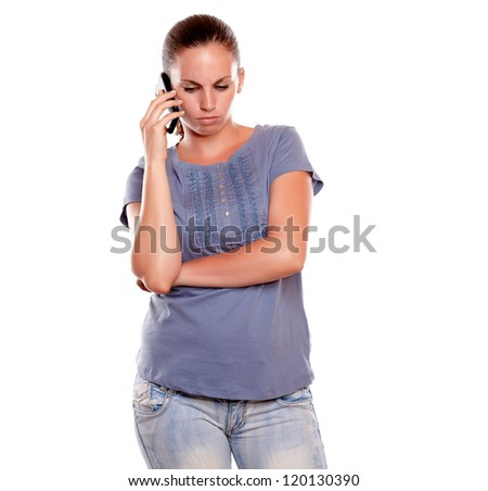 Serious young woman speaking on mobile phone standing over white background - stock photo