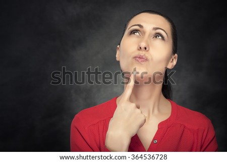 Serious young woman thinking about something on a dark background. - stock photo