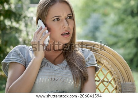 Serious young woman using cell phone on chair in park - stock photo