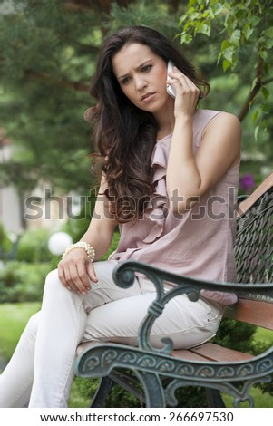 Serious young woman using cell phone on park bench - stock photo