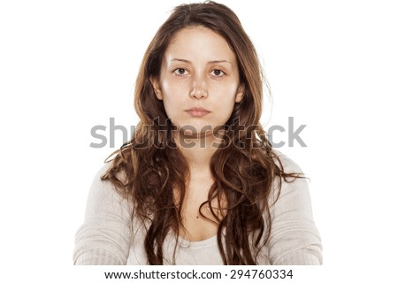 Serious young woman without makeup on a white background - stock photo