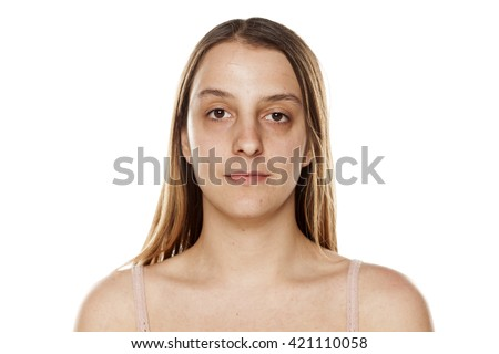 serious young woman without makeup on a white background
