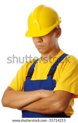 Serious young worker pull hardhat over his eyes, wearing blue-and-yellow uniform, isolated on white - stock photo