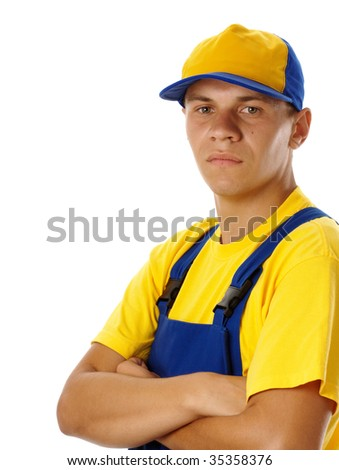 Serious young worker wearing baseball hat and blue-and-yellow uniform, isolated over white - stock photo