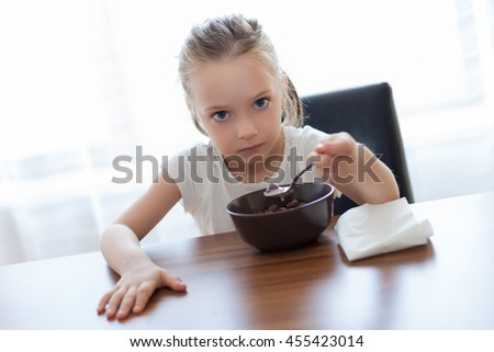 Seriously beautiful little girl eating flakes with milk - stock photo