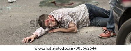 Seriously injured man is lying on street - stock photo