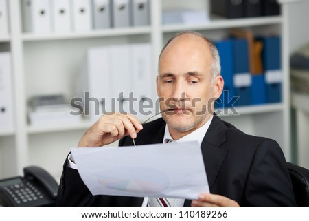 seriously looking businessman studying paper