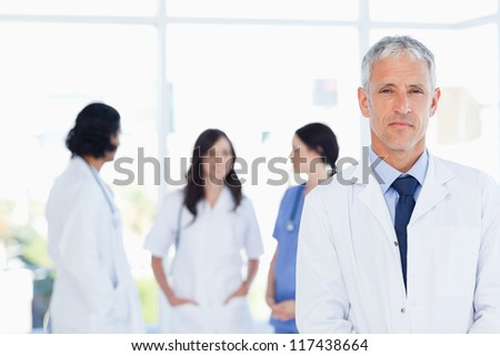 Serous doctor standing in the foreground and accompanied by his team - stock photo