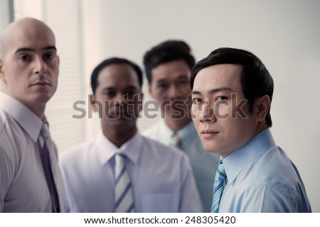 Serous Vietnamese businessman with his colleagues in the background - stock photo