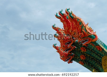 Serpent king or king of naga statue in Thai temple isolated on blue sky background.