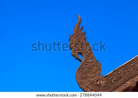 serpent king or king of naga wood carving craft  in thai temple on blue sky background - stock photo