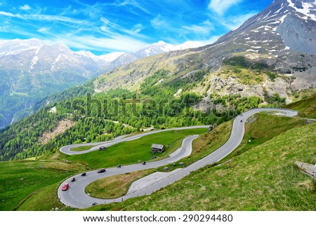 serpentine mountain road winds through  valley - stock photo