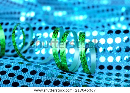 Serpentine ribbon on bright blue fabric background