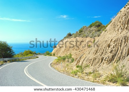 Serpentine road goes down in mountains to Mediterranean Sea in a sunny day on Cyprus island. - stock photo