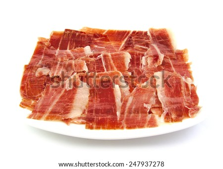 Serrano ham slices on a white dish. Jabugo. Spanish tapa - stock photo