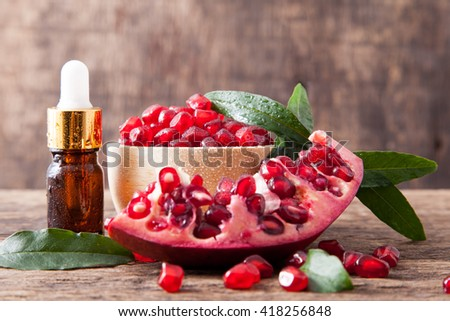 serum bottle or essential oil bottle with fresh pomegranate seeds on wooden table top
