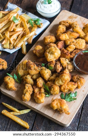 Served chicken nuggets and french sauce on wooden board,selective focus  - stock photo