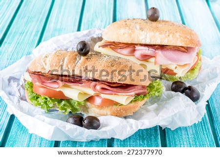 Served ciabatta sandwiches stuffed with meat and cheese,selective focus - stock photo