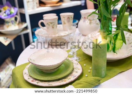 Served fashion green table with glases and plates - stock photo