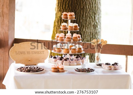 Served festive candy bar table with cupcakes tower