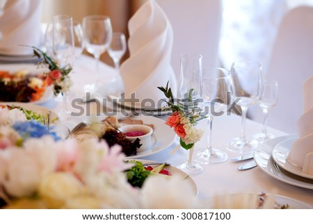 Served for a banquet table. Wine glasses with napkins, glasses and salads. - stock photo
