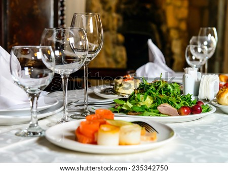 Served for holiday banquet restaurant table with dishes, snack, cutlery, wine and water glasses. European food. - stock photo