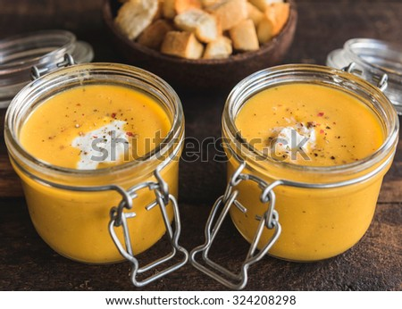 Served homemade pumpkin soups in glass jars, selective focus  - stock photo