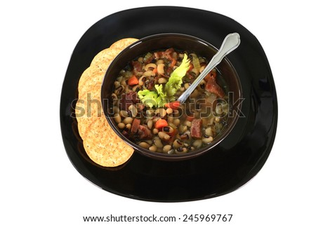 Served in black bowl on dish New Years Day Traditional American South soup, Black-eyed Peas, Chopped Ham Celery Carrot White Onion, Spoon and Crackers over white background