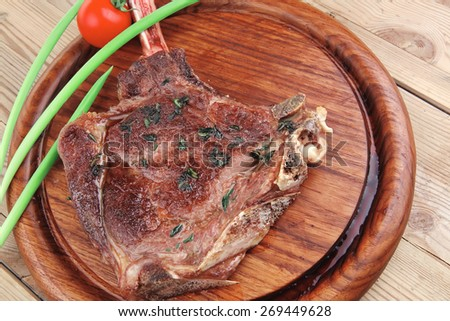 served main course: boned roasted lamb ribs served with green chives and cherry tomato on wooden plate - stock photo