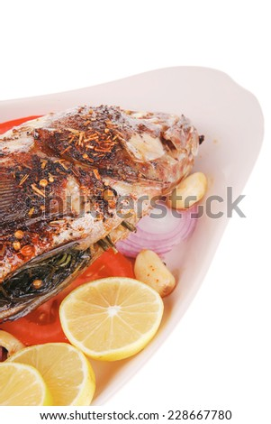 served main course: whole fried seabass served on plate with lemons,tomatoes and peppers . shallow dof - stock photo