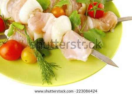 served raw chicken kebabs with tomatoes and peppers - stock photo