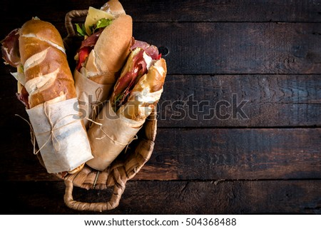 Served sandwiches in the basket on wooden background with blank space
