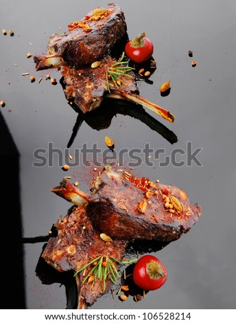 served savory plate: meat ribs with spices and red hot pepper - stock photo