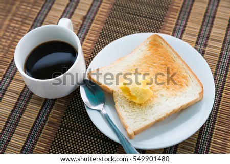 Served table for breakfast with toast, coffee and butter on tablemat