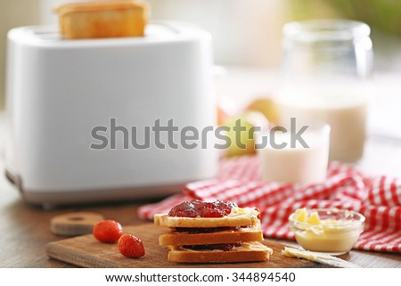 Served table for breakfast with toast, milk and jam, close-up - stock photo