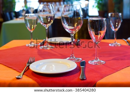 Served table in restaurant. white plate knife fork and wine glasses on red napkin. romantic interior - stock photo