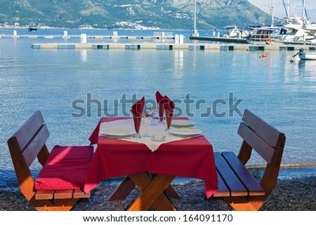 Served table on sea beach restaurant of Budva, Montenegro.  - stock photo