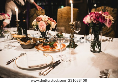 Served table set with flowers and empty wine glasses in french restaurant - stock photo