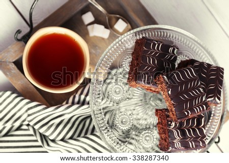 Served table with a cup of tea and chocolate cakes close-up - stock photo