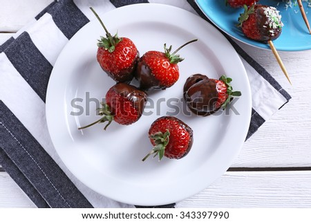 Served table with delicious strawberries in chocolate - stock photo
