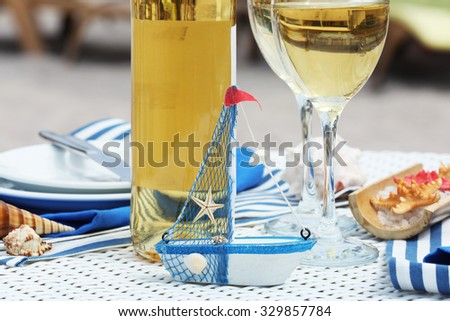 Served table with wine bottle and little boat - stock photo